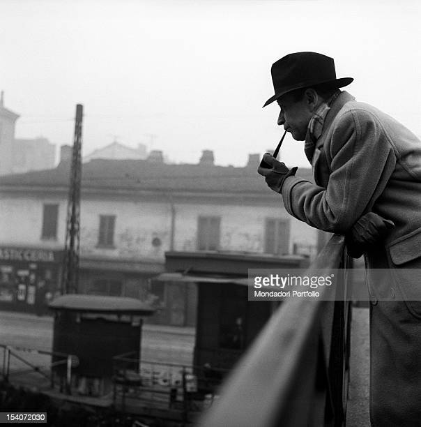 Belgian writer Georges Simenon smoking the pipe on a bridge Milan 1950s
