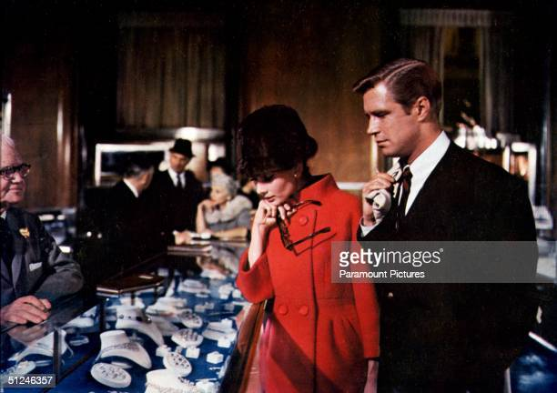 1961 Belgianborn actor Audrey Hepburn and American actor George Peppard browse through jewelry at Tiffany's department store in a scene from director...
