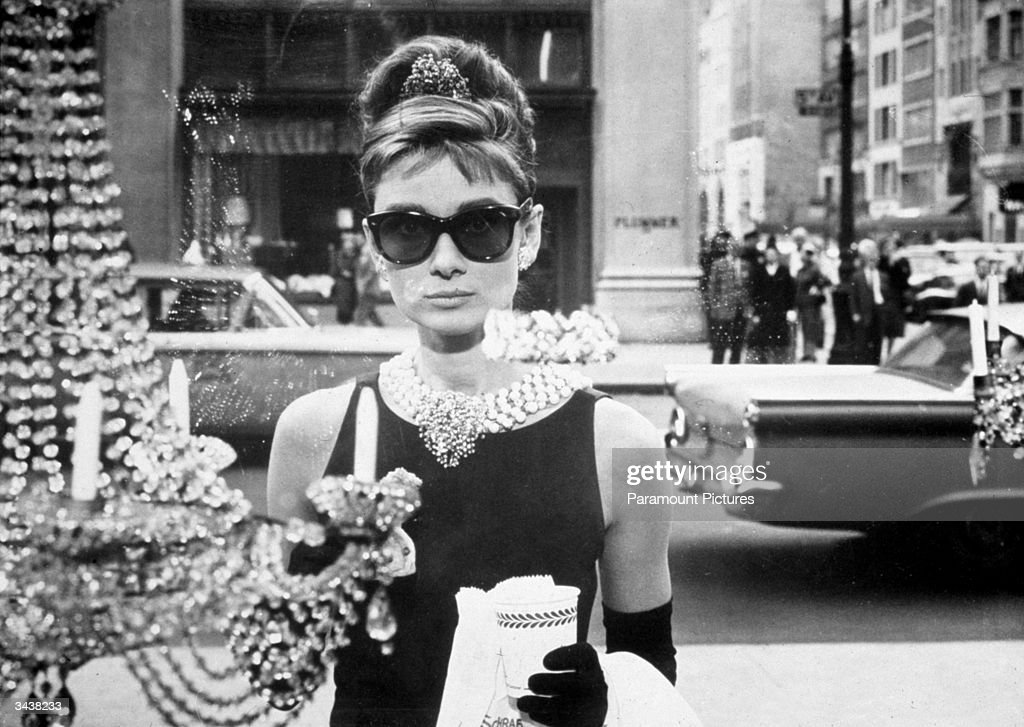 Belgian-born actor Audrey Hepburn (1929 - 1993), as Holly Golightly, holds a cup and a paper bag while looking into one of the window displays at Tiffany's in a still from the film, 'Breakfast at Tiffany's,' directed by Blake Edwards. She wears sunglasses, a little black dress, long gloves and a tiara in her chignon.