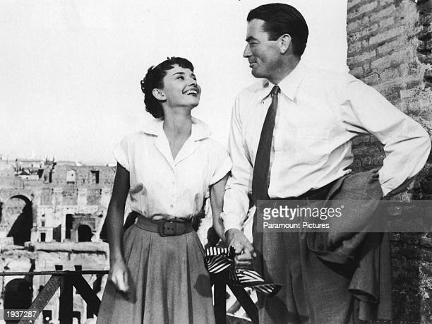 Belgianborn actor Audrey Hepburn holds the hand of American actor Gregory Peck in a still from the film 'Roman Holiday' directed by William Wyler...