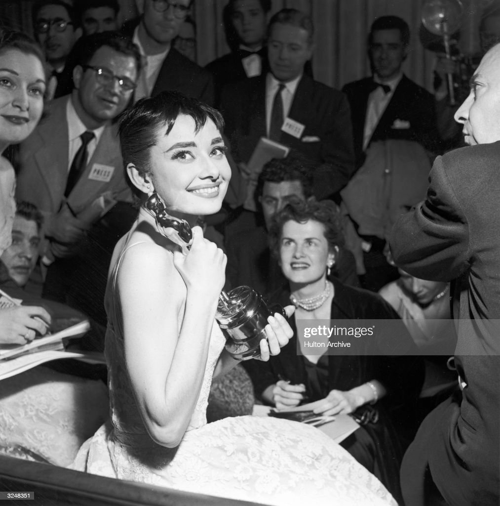 Belgian-born actor Audrey Hepburn (1929 - 1993) is surrounded by reporters as she holds the Best Actress Oscar she won for her role in director William Wyler's film, 'Roman Holiday,' at the Academy Awards ceremony in New York City.