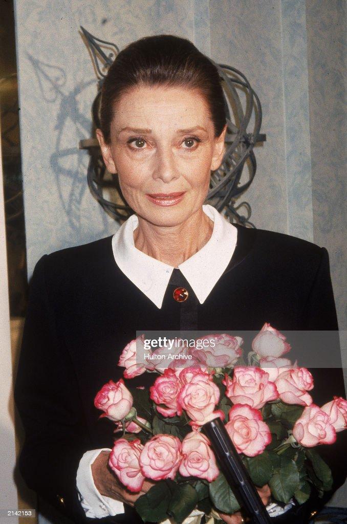 Belgian-born actor Audrey Hepburn (1929 - 1993) stands holding a bouquet of flowers, circa 1985.