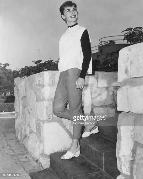 Belgianborn actress Audrey Hepburn circa 1955 She is wearing capri pants and a white tunic with black sleeves
