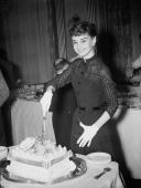 Belgianborn actress Audrey Hepburn cuts into a 'Welcome Home' cake during a reception at Claridges Hotel 21st May 1953 She has just arrived back in...