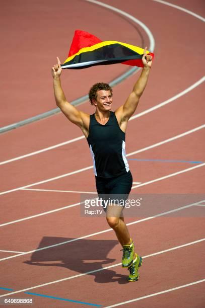 A Belgium Athlete running around athletics track with the Belgium national Flag Celebrating.