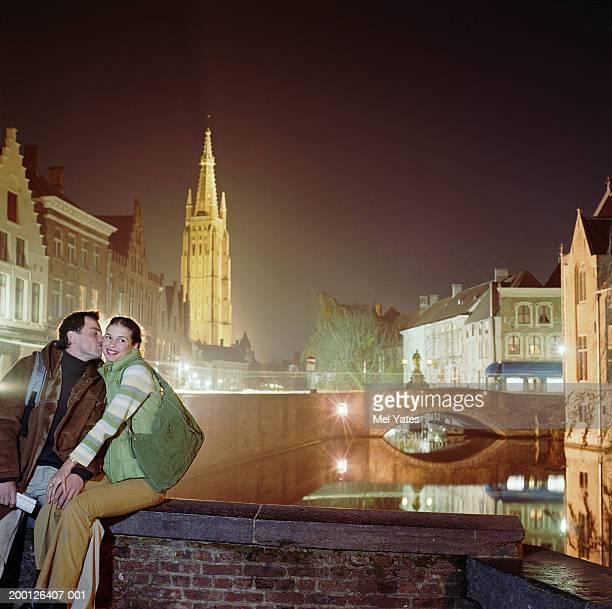 Belgium, Flanders, Bruges, couple on bridge wall, night
