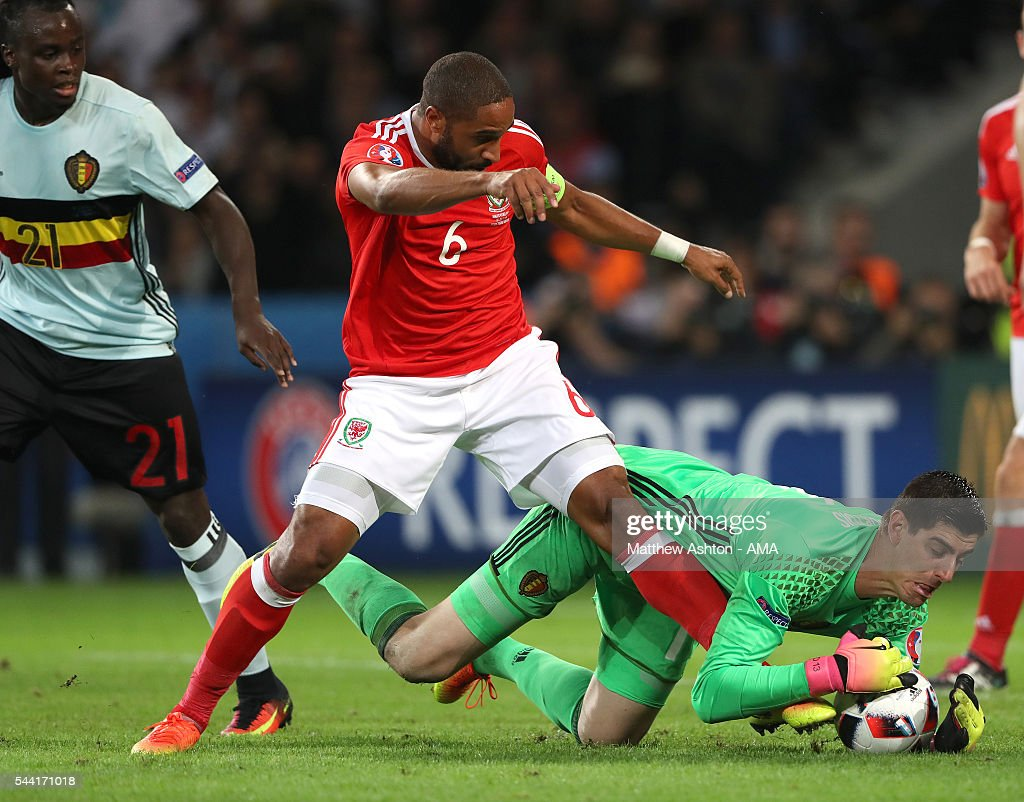 Belgium goalkeeper Thibaut Courtois saves at the feet of Ashley Williams of Wales during the UEFA Euro 2016 quarter final match between Wales and Belgium at Stade Pierre-Mauroy on July 1, 2016 in Lille, France.