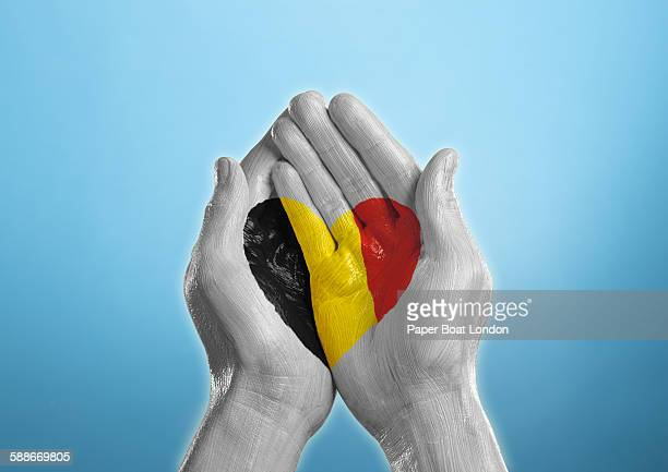 belgium heart shaped flag painted on a hand