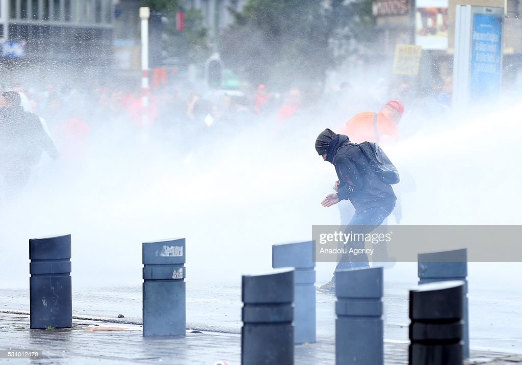 Belgium police fire water cannons to disperse protesters during a national protest on May 24, 2016, in Brussels, Belgium. Belgian trade unions called for mass protest against the center-right government's social and economic policies.