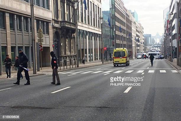 Belgium police officers block a street in Brussels on March 22 2016 after an explosion occurred at a metro station At least 13 people have been...
