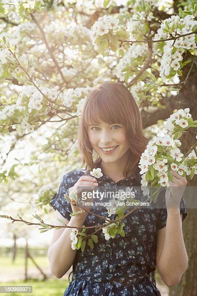 Belgium, Sint-Truiden, Portrait of young woman in blooming orchard