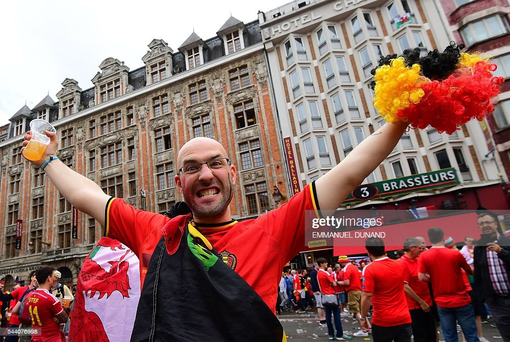 A Belgium supporter cheers in the streets of Lille on July 1, 2016 before the Euro 2016 quarter-final football match between Wales and Belgium. / AFP / EMMANUEL