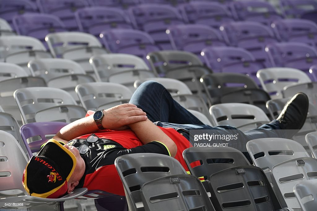 A Belgium supporter lies on seats prior to the Euro 2016 round of 16 football match between Hungary and Belgium at the Stadium Municipal in Toulouse on June 26, 2016. / AFP / PASCAL