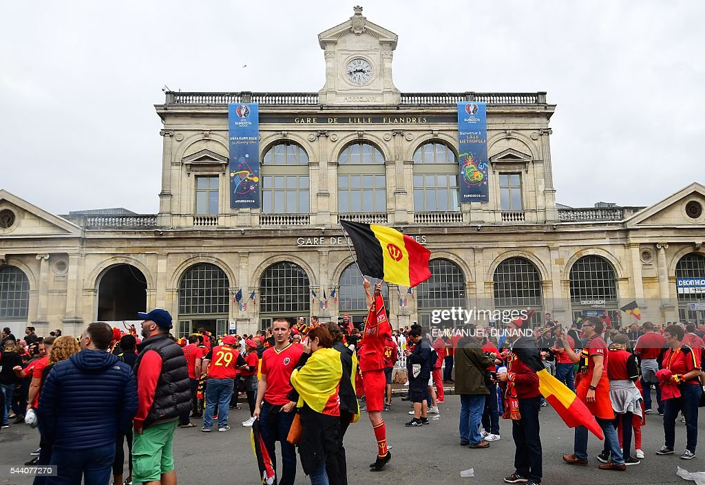 Belgium supporters cheer in front of Lille's train station on July 1, 2016 before the Euro 2016 quarter-final football match between Wales and Belgium. / AFP / EMMANUEL