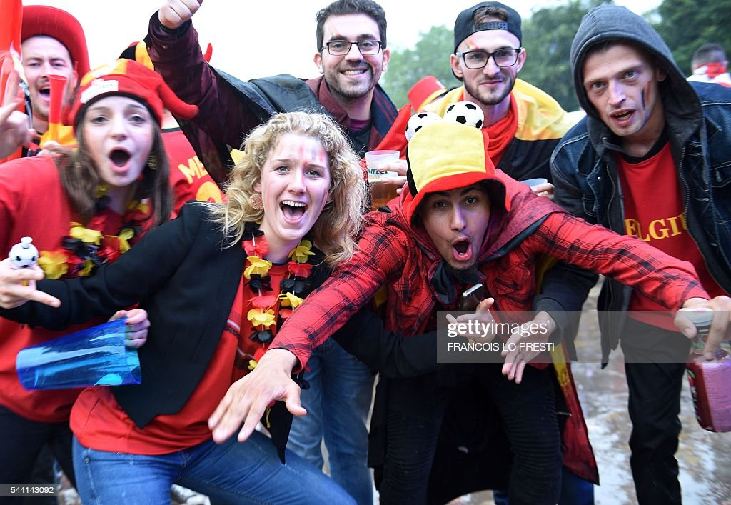 Belgium supporters pose at the fanzone on General De Gaulle square in Lille on July 1, 2016 as they watch the Euro 2016 quarter-final football match between Wales and Belgium. / AFP / FRANCOIS