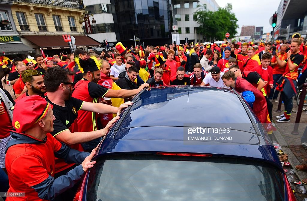 Belgium supporters surround a car in a street of Lille on July 1, 2016 before the Euro 2016 quarter-final football match between Wales and Belgium. / AFP / EMMANUEL