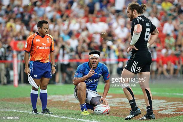 Belgium Tuatagaloa of Samoa gestures after scoring a try as Gillies Kaka of New Zealand looks on during the 2016 Singapore Sevens Plate Final between...