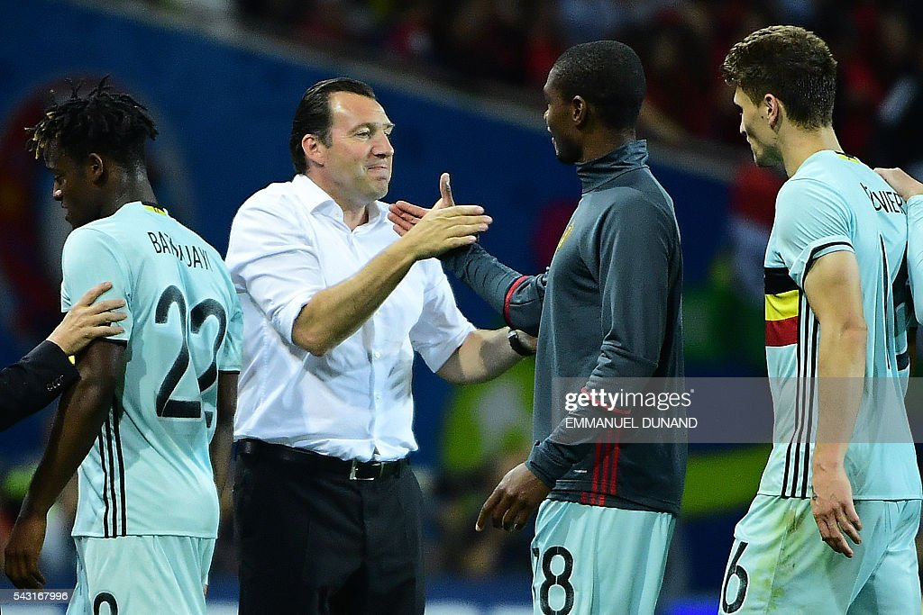 Belgium's coach Marc Wilmots (2L) shakes hands with Belgium's defender Christian Kabasele (2R) after winning the Euro 2016 round of 16 football match between Hungary and Belgium at the Stadium Municipal in Toulouse on June 26, 2016. / AFP / EMMANUEL