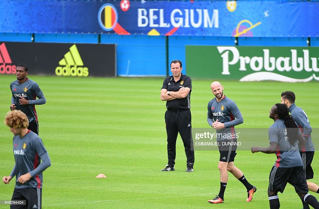 Belgium's coach Marc Wilmots (C) watches his players during a training session in Le Haillan, southwestern France, on June 27, 2016, ahead of their Euro 2016 quarter-final football match against Wales. / AFP / EMMANUEL