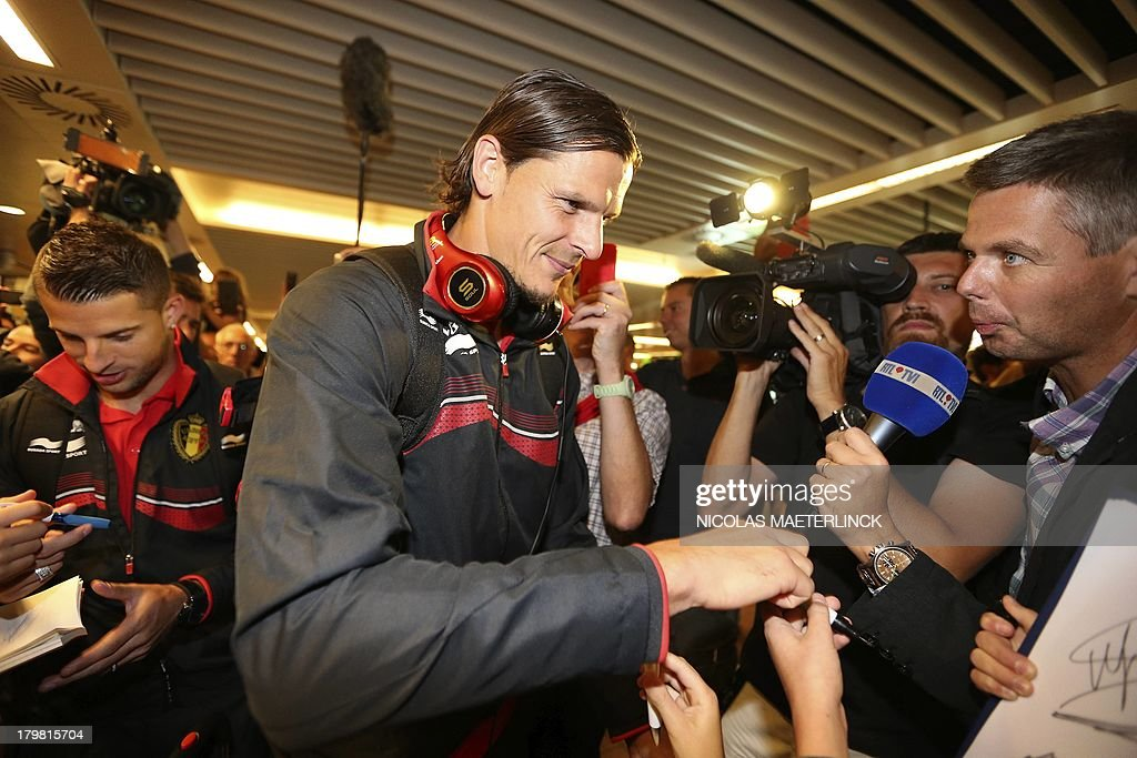 Belgium's Daniel Van Buyten signs autographs as the Red Devils football team arrive at Brussels airport in Zaventem, on September 7, 2013, the day after winning the WC2014 qualifying match against Scotland.