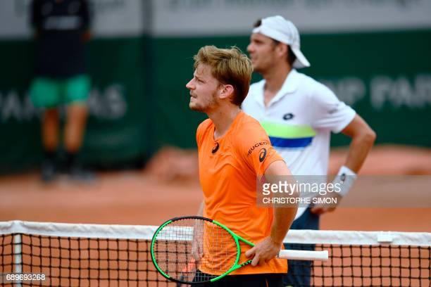 Belgium's David Goffin and France's PaulHenri Mathieu look on during their tennis match at the Roland Garros 2017 French Open on May 29 2017 in Paris...