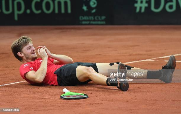 Belgium's David Goffin lies on the court as he reacts after beating Australia's Nick Kyrgios during the Davis Cup semifinal between Belgium and...