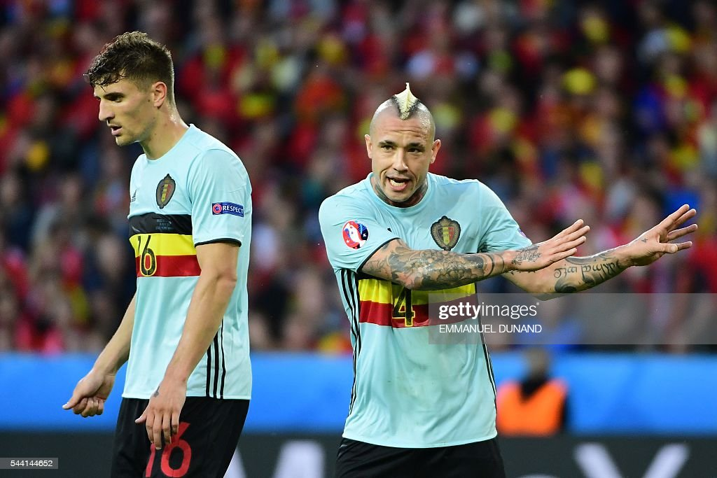 Belgium's defender Thomas Meunier (L) and Belgium's midfielder Radja Nainggolan react during the Euro 2016 quarter-final football match between Wales and Belgium at the Pierre-Mauroy stadium in Villeneuve-d'Ascq near Lille, on July 1, 2016. / AFP / EMMANUEL