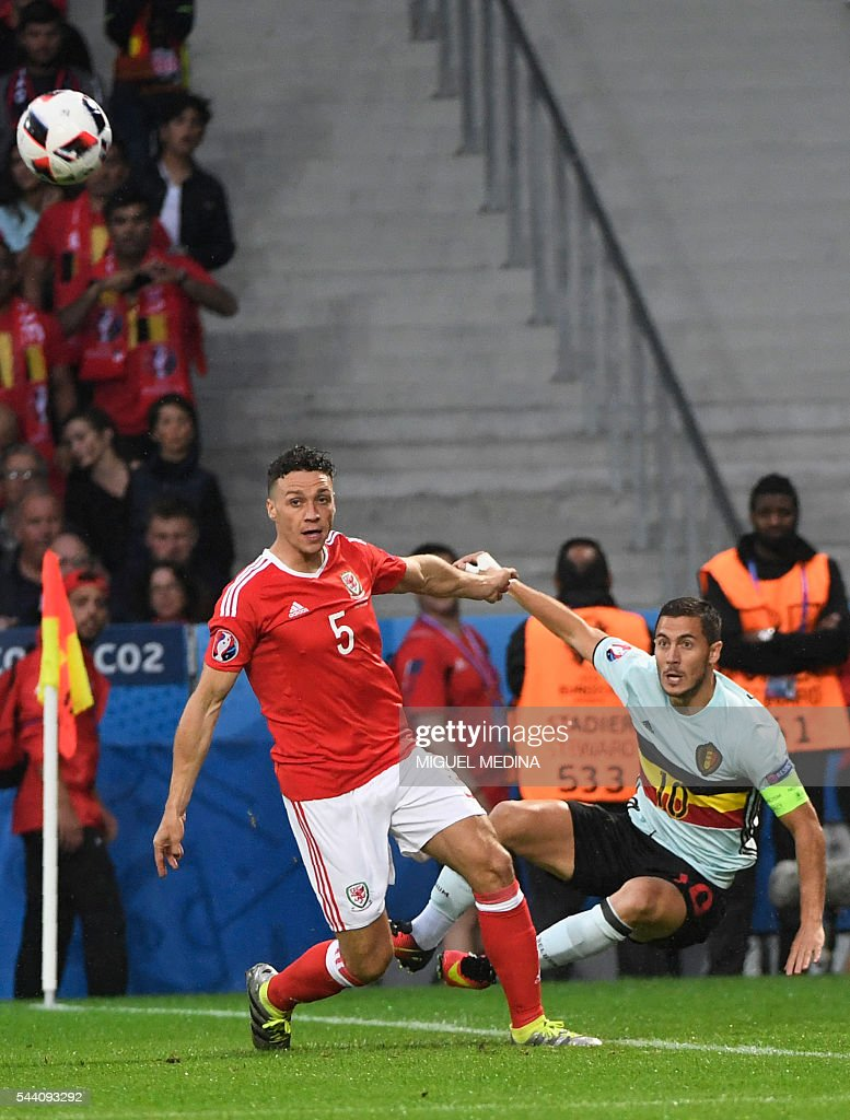 Belgium's forward Eden Hazard challenges Wales' defender James Chester (L) during the Euro 2016 quarter-final football match between Wales and Belgium at the Pierre-Mauroy stadium in Villeneuve-d'Ascq near Lille, on July 1, 2016. / AFP / MIGUEL