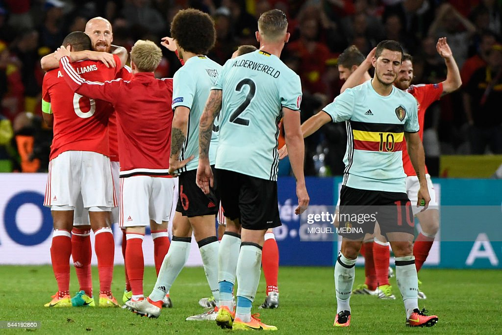 Belgium's forward Eden Hazard (R) reacts next to Wales' players as they celebrate at the end of the Euro 2016 quarter-final football match between Wales and Belgium at the Pierre-Mauroy stadium in Villeneuve-d'Ascq near Lille, on July 1, 2016. / AFP / MIGUEL