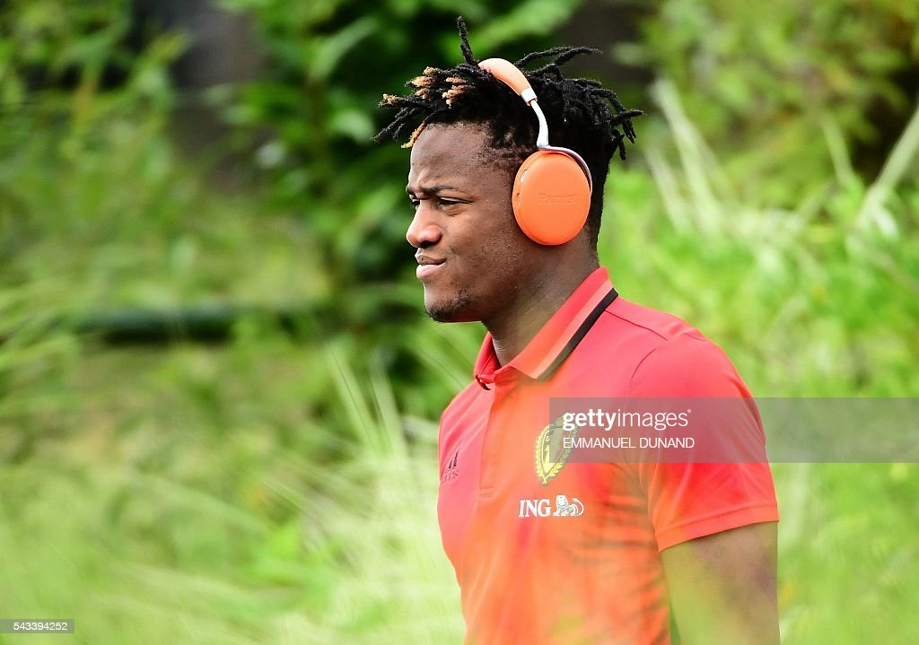 Belgium's forward Michy Batshuayi arrives to take part in a training session during the Euro 2016 football tournament at Le Haillan, France, on June 28, 2016. At L is security personel. / AFP / EMMANUEL