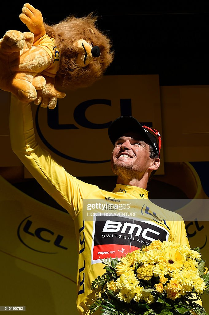 Belgium's Greg Van Avermaet celebrates his overall leader yellow jersey on the podium at the end of the 216 km fifth stage of the 103rd edition of the Tour de France cycling race on July 6, 2016 between Limoges and Le Lioran. / AFP / LIONEL