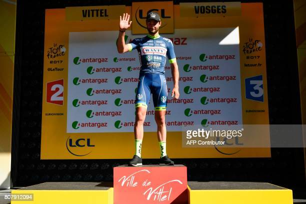 Belgium's Guillaume Van Keirsbulck celebrates his combativity prize on the podium at the end of the 2075 km fourth stage of the 104th edition of the...