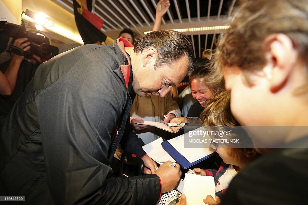 Belgium's head coach Marc Wilmots signs autographs as the Red Devils football team arrive at Brussels airport in Zaventem, on September 7, 2013, the day after winning the WC2014 qualifying match against Scotland.
