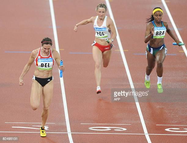 Belgium's Kim Gevaert croses the finish line ahead of Poland's Marta Jeschke and Brazil's Rosangela Santos during the women's 4x100m Relay round 1...