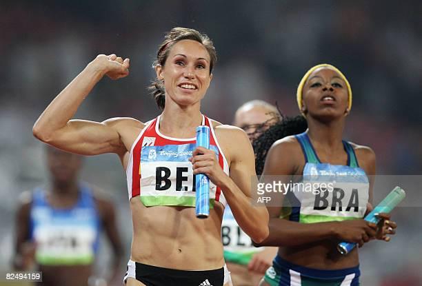 Belgium's Kim Gevaert jubilates as she crosses the finishline ahead of Brazil's Rosangela Santos during the women's first round 4x100m relay heat 1...