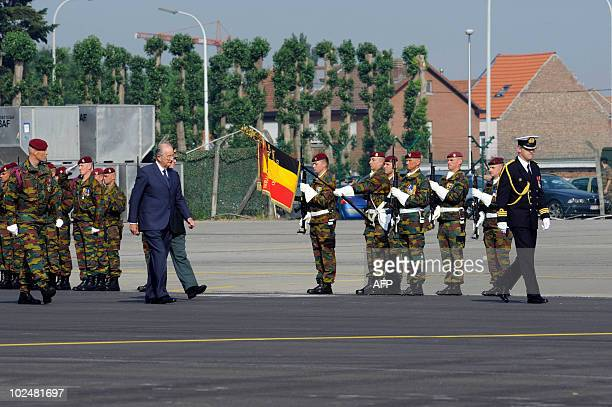 Belgium's King Albert II walks on the tarmac past guards of honour holding the Belgian flag before boarding a plane to Kinshasa at the military...
