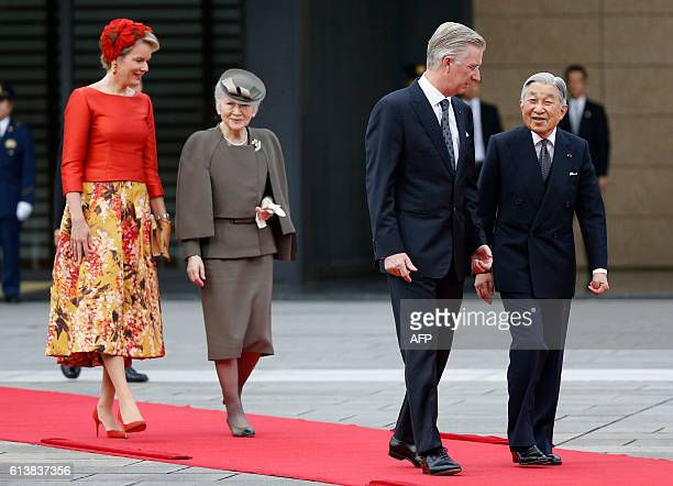 Belgium's King Philippe and Queen Mathilde are escorted by Japan's Emperor Akihito and Empress Michiko on the red carpet during a welcoming ceremony...