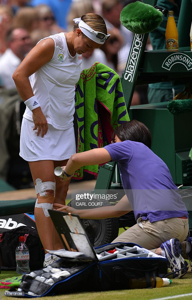 Belgium's Kirsten Flipkens receives some attention to her leg between games against France's Marion Bartoli during their women's singles semi-final match on day ten of the 2013 Wimbledon Championships tennis tournament at the All England Club in Wimbledon, southwest London, on July 4, 2013.