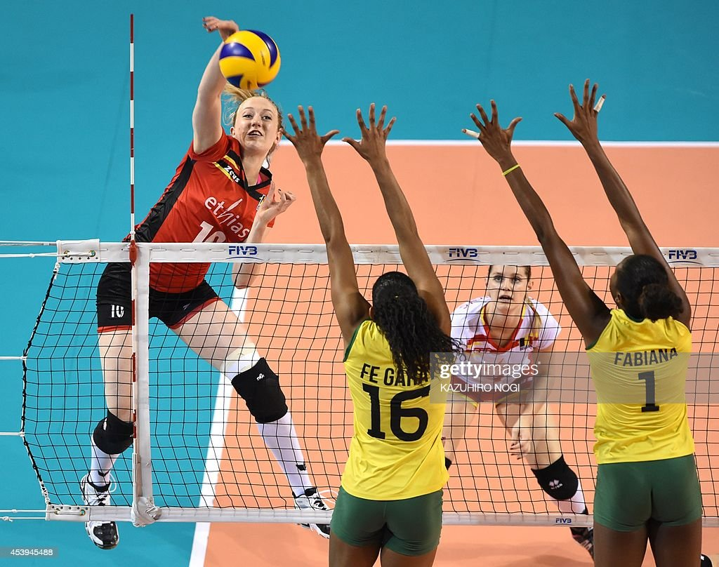 Belgium's Lise Van Hecke spikes the ball over Brazil's Fernanda Rodrigues and Fabiana Claudino during their volleyball match of the FIVB Women's...