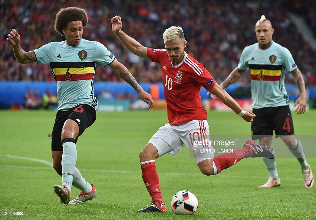 Belgium's midfielder Axel Witsel (L) and Belgium's midfielder Radja Nainggolan (R) challenge Wales' midfielder Aaron Ramsey during the Euro 2016 quarter-final football match between Wales and Belgium at the Pierre-Mauroy stadium in Villeneuve-d'Ascq near Lille, on July 1, 2016. / AFP / PHILIPPE
