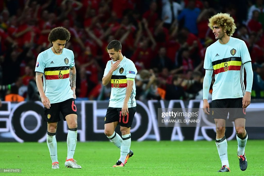 Belgium's midfielder Axel Witsel, Belgium's forward Eden Hazard and Belgium's midfielder Marouane Fellaini react after the Euro 2016 quarter-final football match between Wales and Belgium at the Pierre-Mauroy stadium in Villeneuve-d'Ascq near Lille, on July 1, 2016. Wales won the match 3-1. / AFP / EMMANUEL