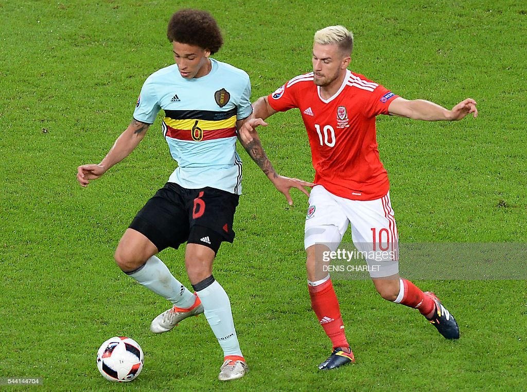 Belgium's midfielder Axel Witsel (R) challenges Wales' midfielder Aaron Ramsey during the Euro 2016 quarter-final football match between Wales and Belgium at the Pierre-Mauroy stadium in Villeneuve-d'Ascq near Lille, on July 1, 2016. / AFP / Denis Charlet