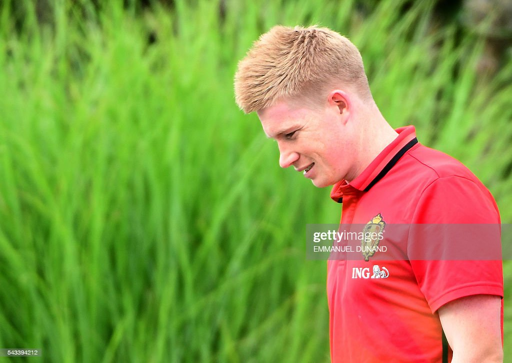Belgium's midfielder Kevin De Bruyne arrives to take part in a training session during the Euro 2016 football tournament at Le Haillan, France, on June 28, 2016. At L is security personel. / AFP / EMMANUEL