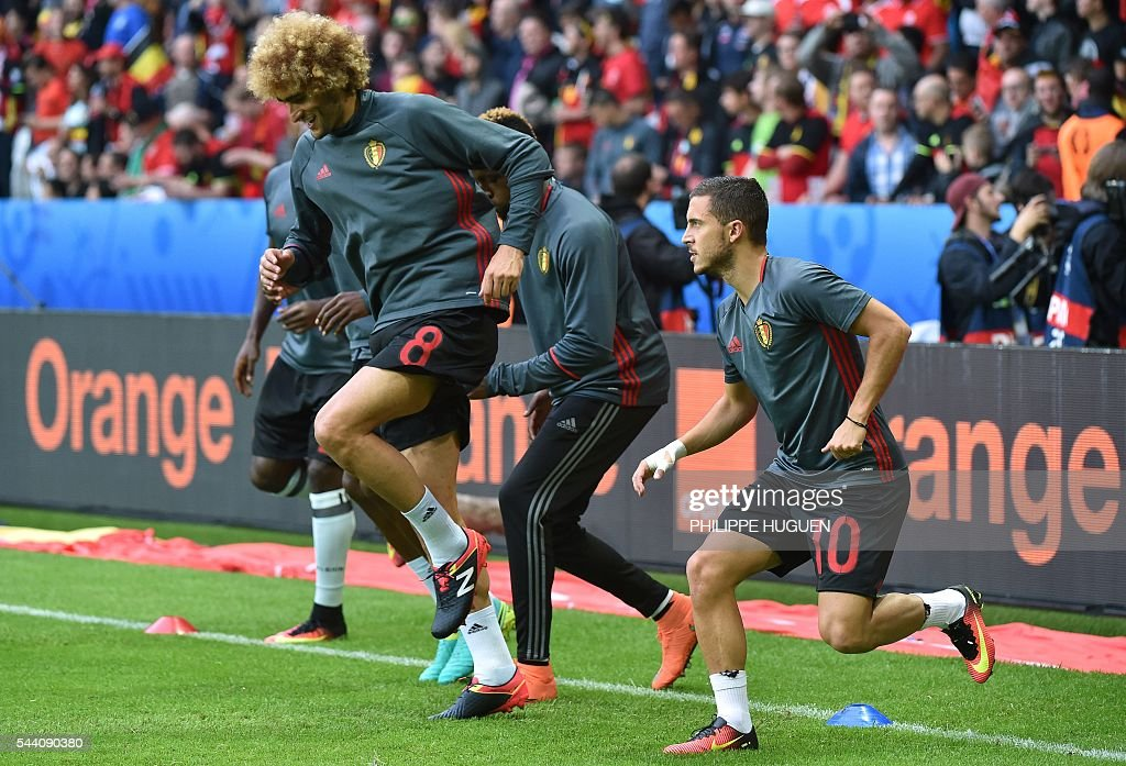Belgium's midfielder Marouane Fellaini and Belgium's forward Eden Hazard (R) warm up with teammates ahead of the Euro 2016 quarter-final football match between Wales and Belgium at the Pierre-Mauroy stadium in Villeneuve-d'Ascq near Lille, on July 1, 2016. / AFP / PHILIPPE