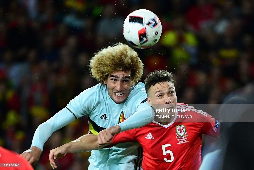 Belgium's midfielder Marouane Fellaini and Wales' defender James Chester vie for the ball during the Euro 2016 quarter-final football match between Wales and Belgium at the Pierre-Mauroy stadium in Villeneuve-d'Ascq near Lille, on July 1, 2016. / AFP / EMMANUEL
