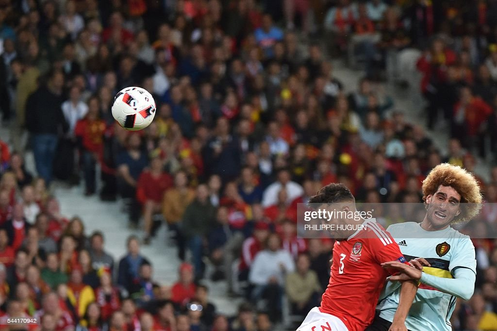 Belgium's midfielder Marouane Fellaini (R) challenges Wales' defender Neil Taylor during the Euro 2016 quarter-final football match between Wales and Belgium at the Pierre-Mauroy stadium in Villeneuve-d'Ascq near Lille, on July 1, 2016. / AFP / PHILIPPE