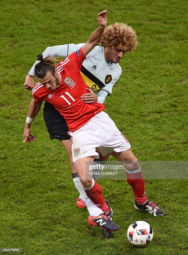 Belgium's midfielder Marouane Fellaini (back) challenges Wales' forward Gareth Bale during the Euro 2016 quarter-final football match between Wales and Belgium at the Pierre-Mauroy stadium in Villeneuve-d'Ascq near Lille, on July 1, 2016. / AFP / DENIS