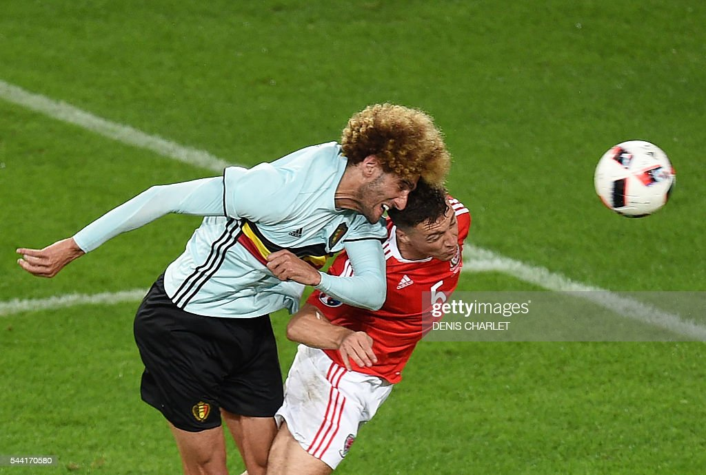 Belgium's midfielder Marouane Fellaini (L) heads the ball with Wales' defender James Chester during the Euro 2016 quarter-final football match between Wales and Belgium at the Pierre-Mauroy stadium in Villeneuve-d'Ascq near Lille, on July 1, 2016. / AFP / DENIS