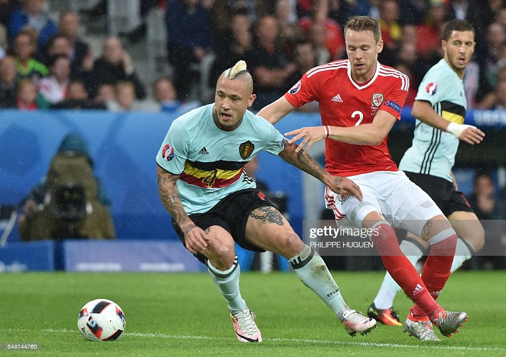 Belgium's midfielder Radja Nainggolan (L) challenges Wales' defender Chris Gunter during the Euro 2016 quarter-final football match between Wales and Belgium at the Pierre-Mauroy stadium in Villeneuve-d'Ascq near Lille, on July 1, 2016. / AFP / PHILIPPE