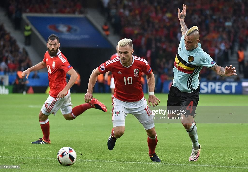 Belgium's midfielder Radja Nainggolan (R) challenges Wales' midfielder Aaron Ramsey during the Euro 2016 quarter-final football match between Wales and Belgium at the Pierre-Mauroy stadium in Villeneuve-d'Ascq near Lille, on July 1, 2016. / AFP / PHILIPPE